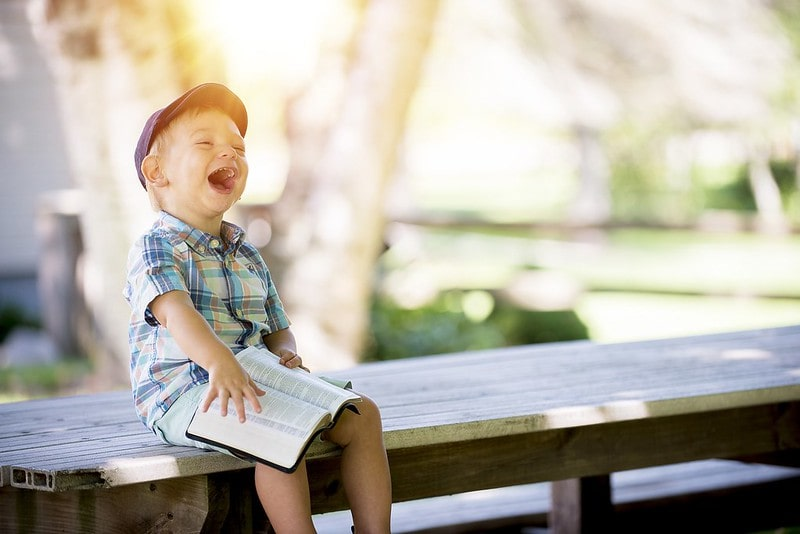 Little boy sat on top of a picnic bench with a book on his lap laughing.