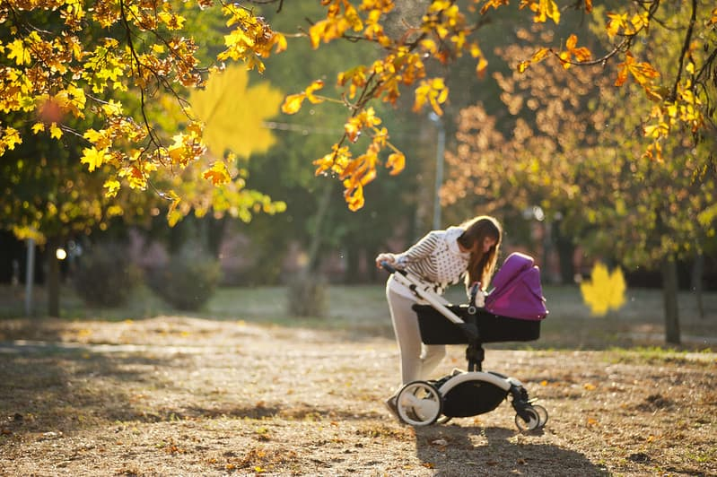 Mum looking at her baby in the stroller on a walk in the park.