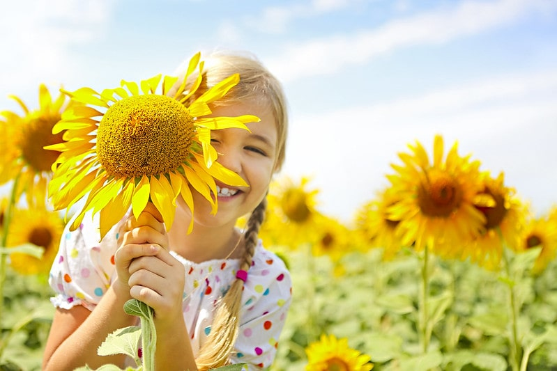 Girl in a sunflower field smiling with a sunflower in front of her face.