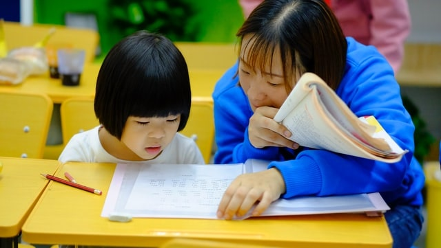 Mother and daughter studying, looking at exercise books.