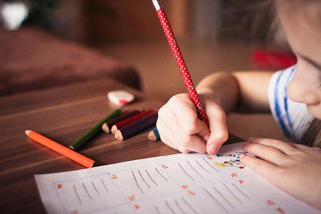 Little girl drawing on her worksheet.