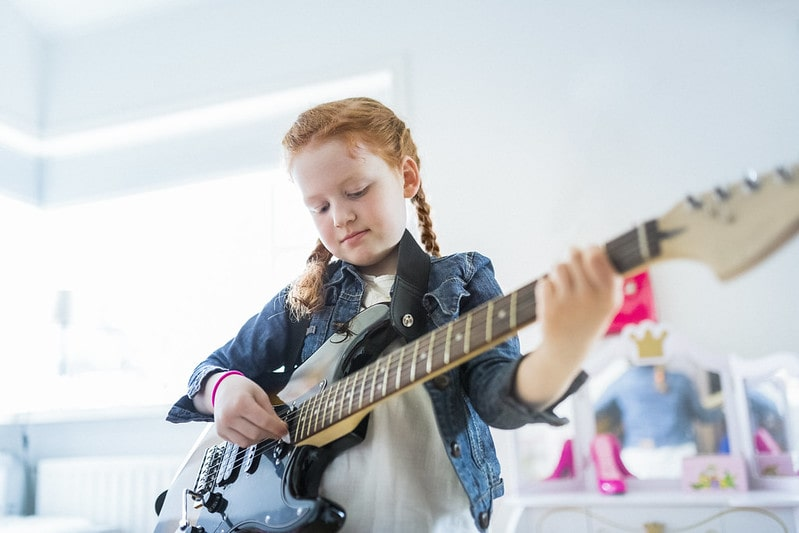 Young girl playing an electric guitar.