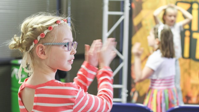 Girl wearing striped top and flower hairband claps.