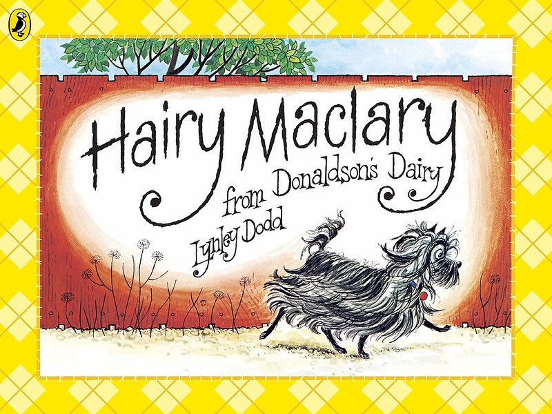 Cover of Hairy Maclary: a black dog with a long coat is walking down a path, with a tall red fence behind it.