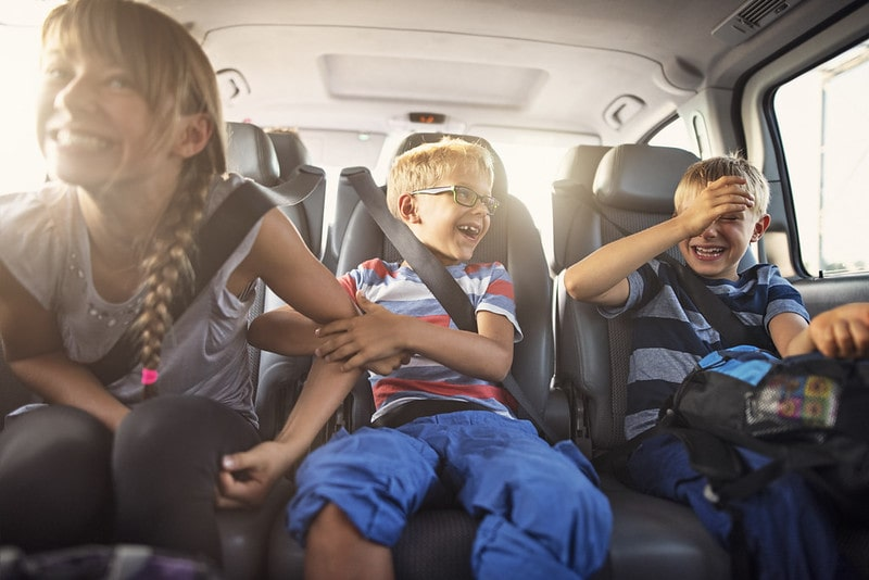 Three kids sitting in the back of the car laughing.