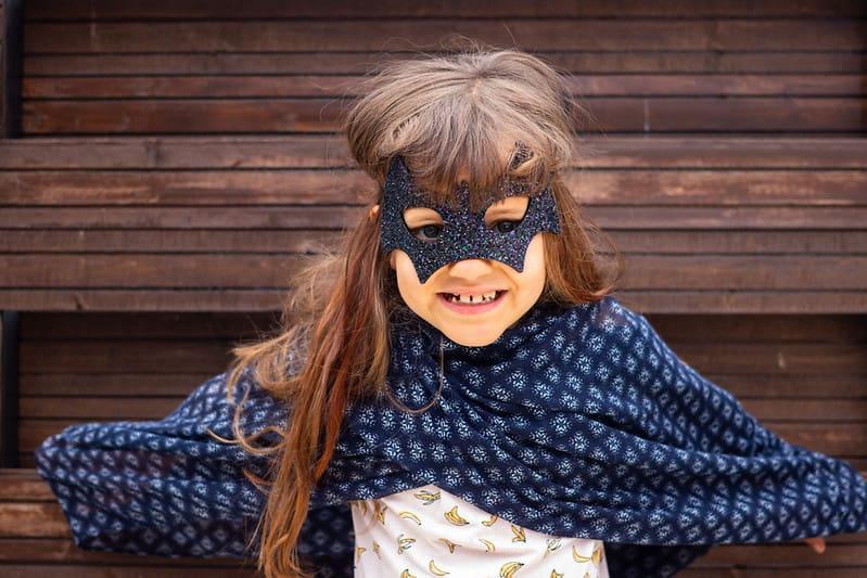 Little girl wearing a glittery bat mask and a makeshift cloak.