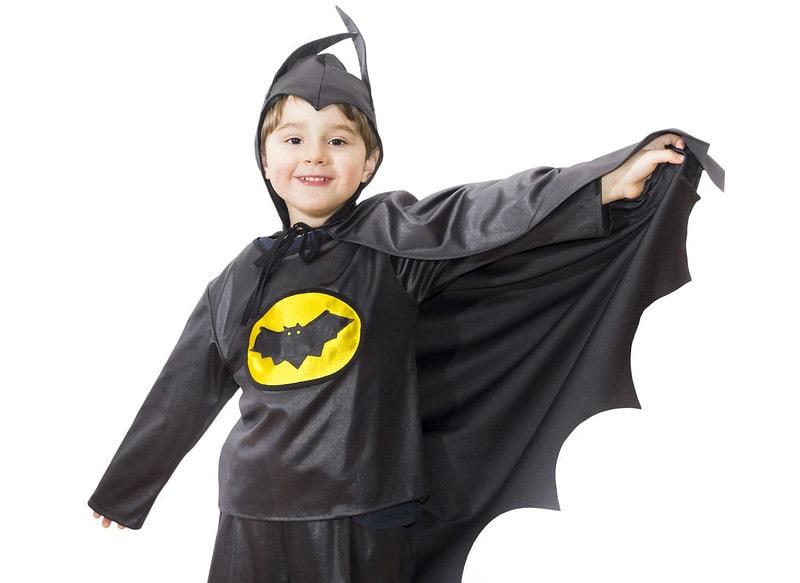 Young boy wearing a batman costume smiling.