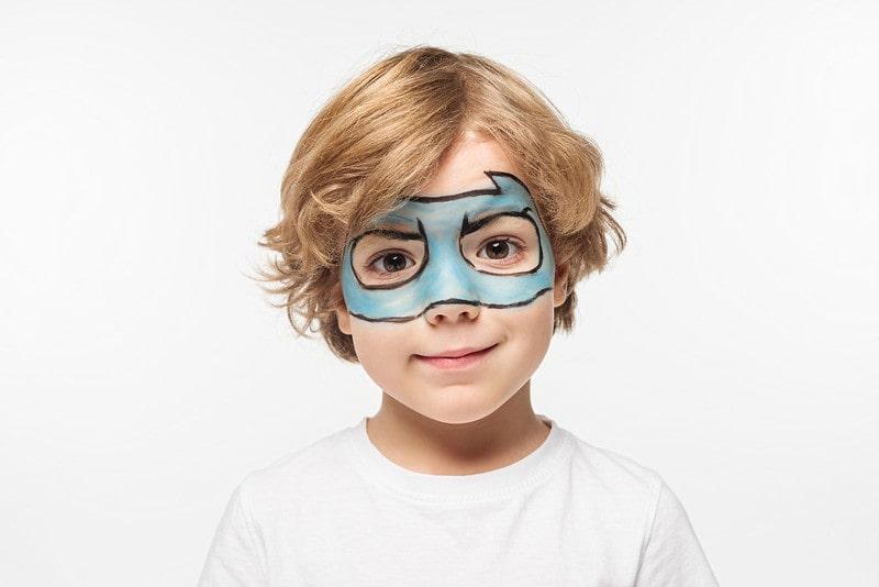 Boy with face paint of a blue batman mask.