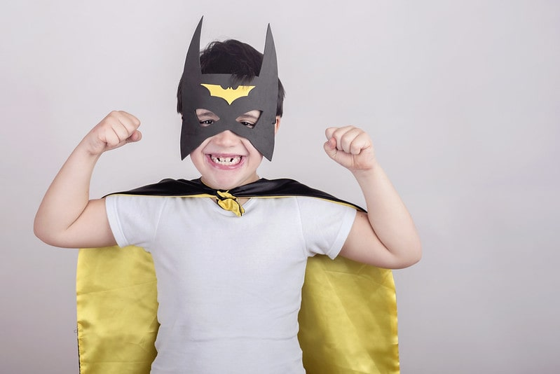 Young boy wearing a homemade batman mask with fists in the air.