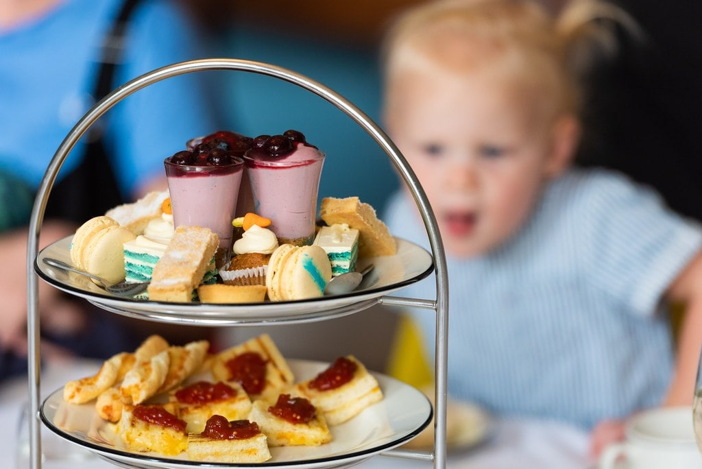 Child looking at the food at a family-friendly afternoon tea in Norwich.