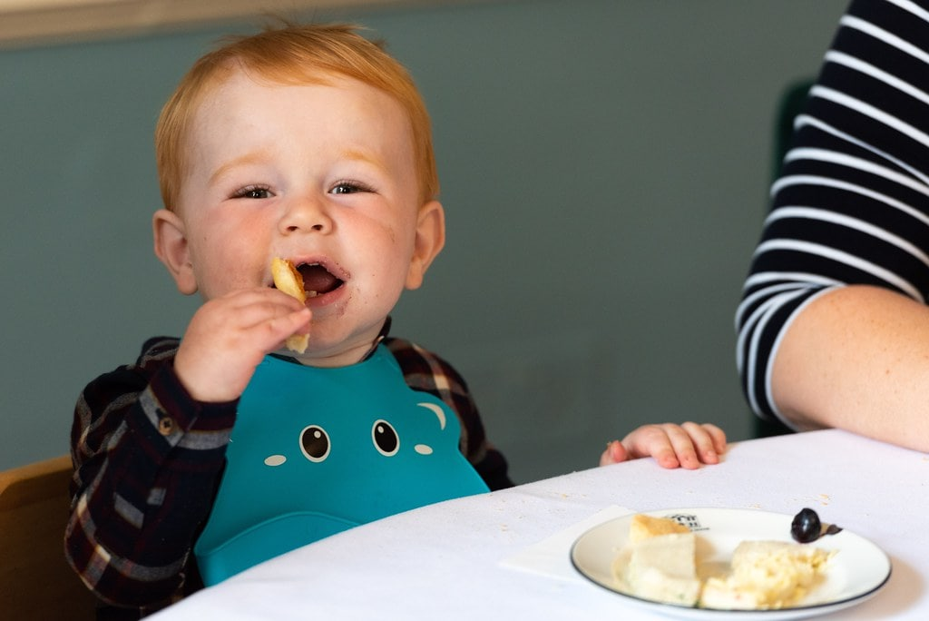Young child enjoying food at a family-friendly afternoon tea.