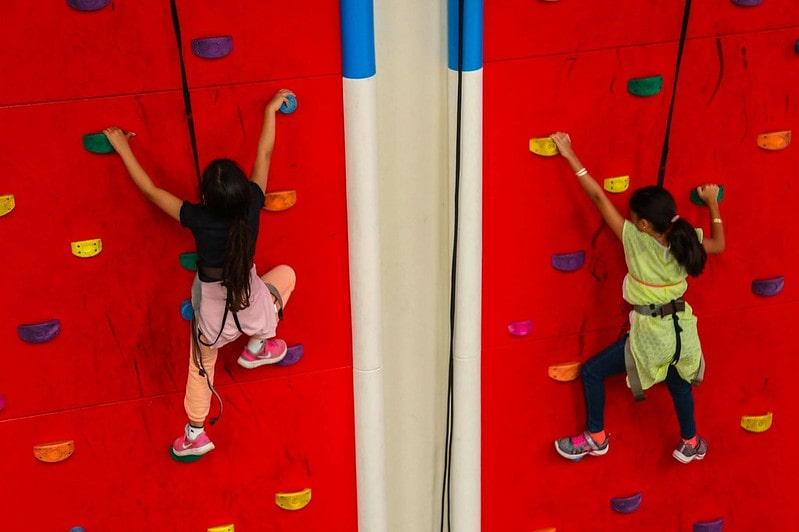 Two girls scaling the climbing walls at Clip 'N Climb.