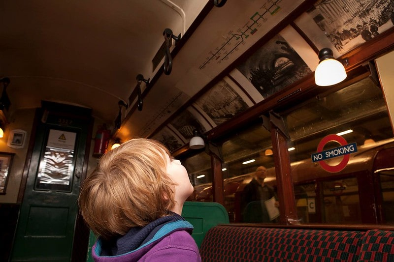 Boy looking at a display in an old train at the London Transport Museum.