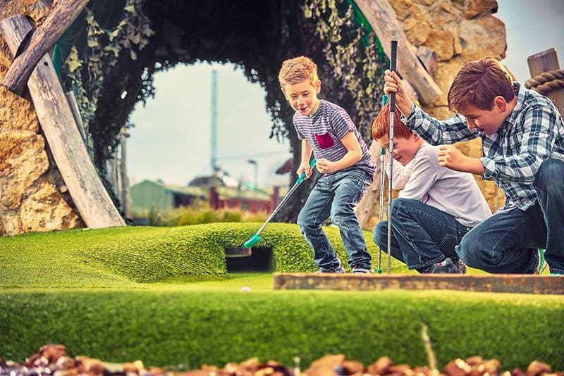 Boys playing crazy golf outdoors.