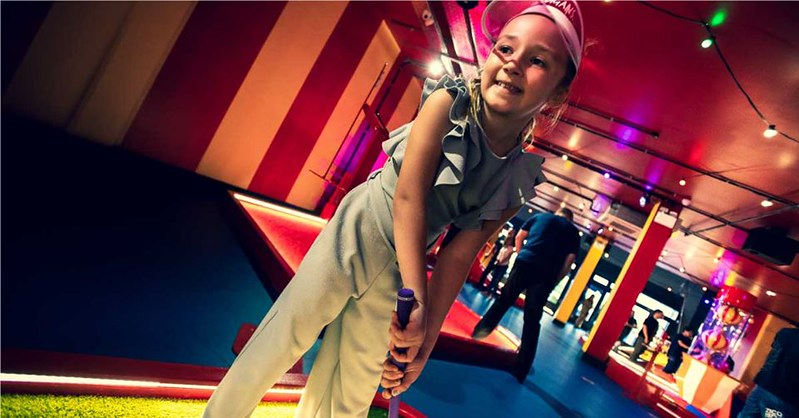 Girl playing crazy golf on a colourful indoor course.