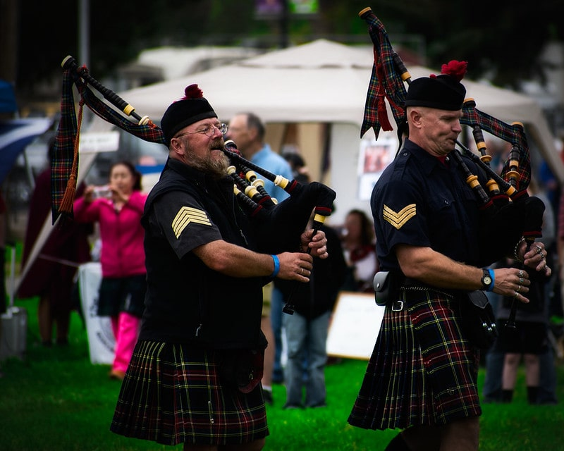 Men in traditional Scottish dress playing the bagpipes.