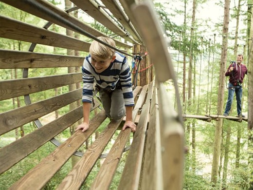 Young boy walking through a wooden tunnel high up in the trees at Go Ape.