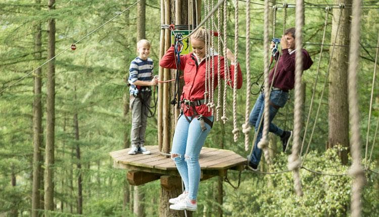 Girl making her way through the treetop course at Go Ape.