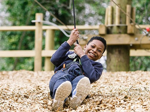 Boy having fun swinging on a rope at Go Ape.