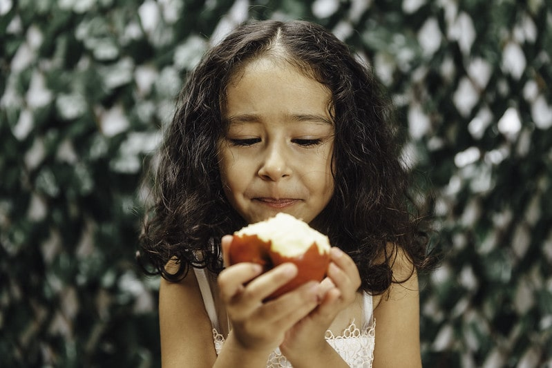 Girl looking at a bitten apple in her hands.