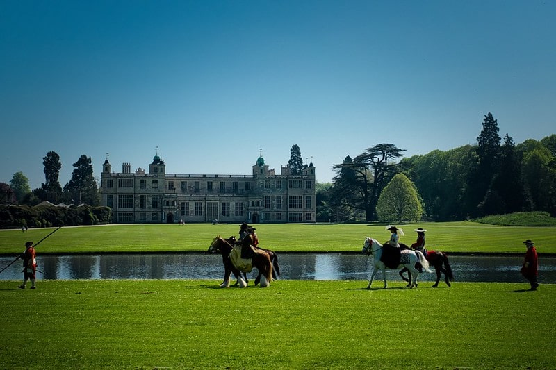 The serpentine lake at Audley End with costumed actors on horses in the forefront at Audley End House and Gardens.