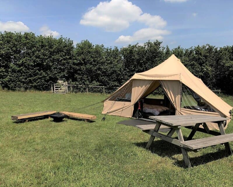 Luxury tent at Arniss Bell Tents with a bell inside and picnic table outside.