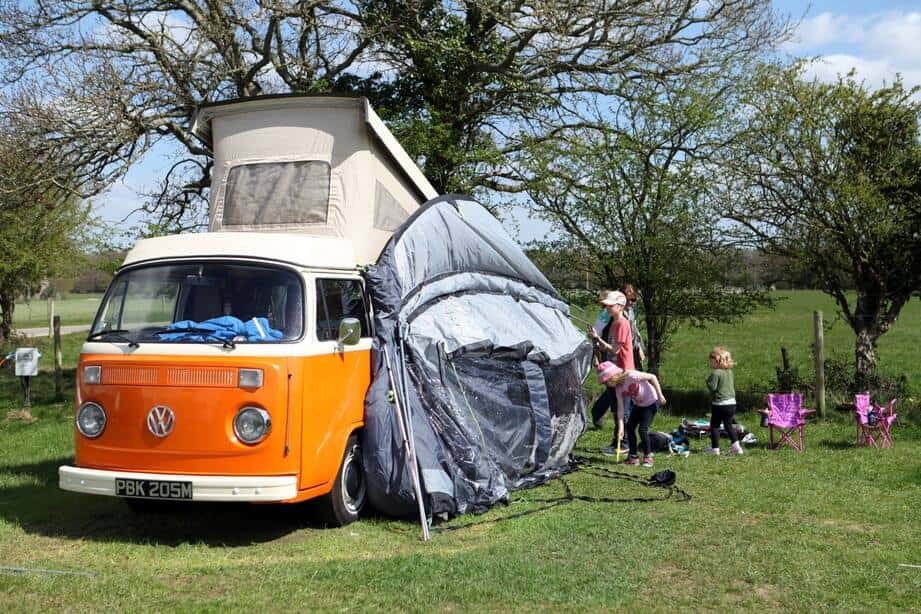 Family setting up their tent from their camper-van.