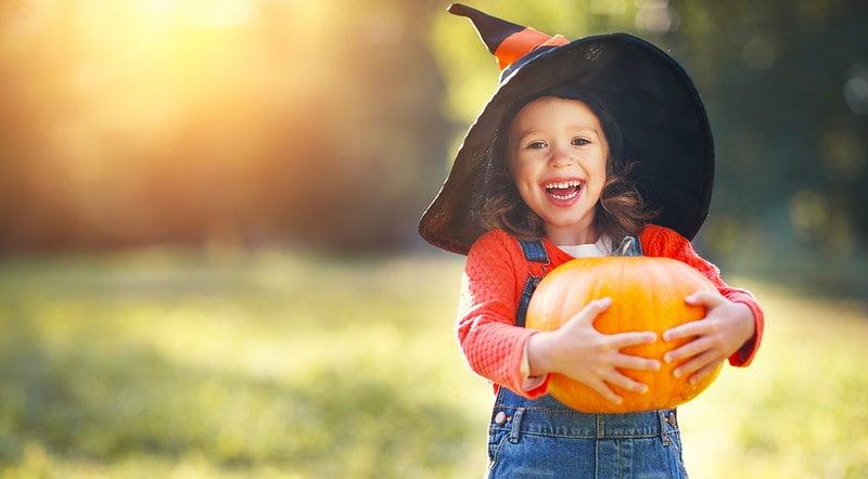 Young girl dressed for Halloween holding a pumpkin smiling.