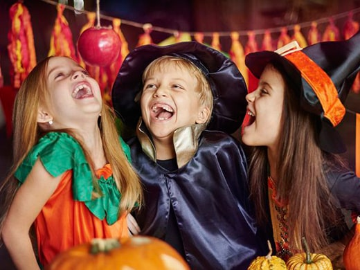Three kids dressed up in Halloween costumes laughing.