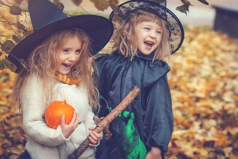 Two small girls in witch outfits laughing with a pumpkin.