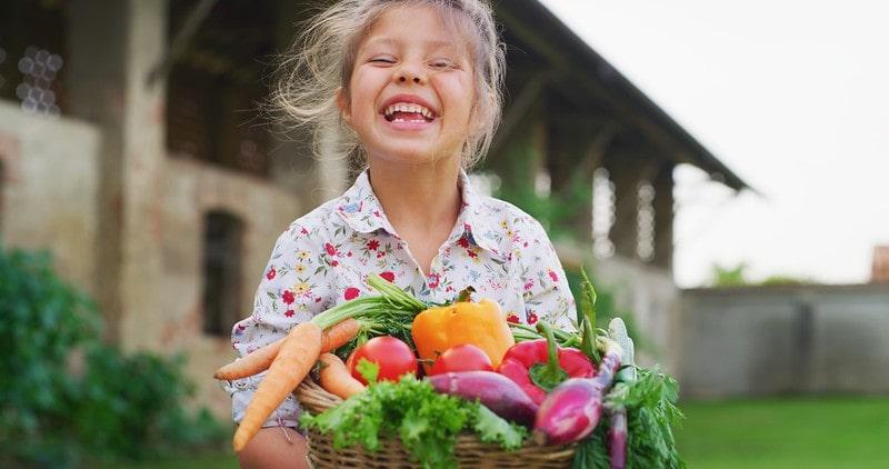 Little girl holding a basket of vegetables smiling.