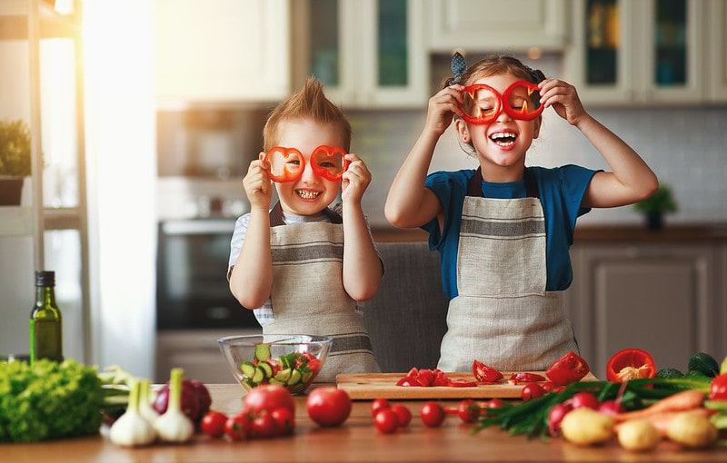 Kids in the kitchen making funny faces with salad, laughing.