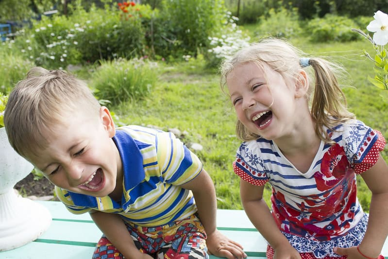 Little boy and girl sitting on a bench in the garden laughing.