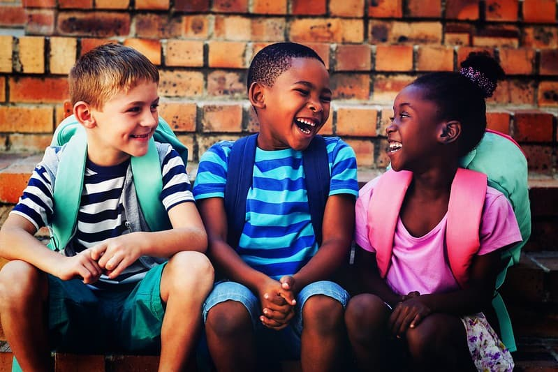 Three school children sitting by a wall laughing at donkey jokes.