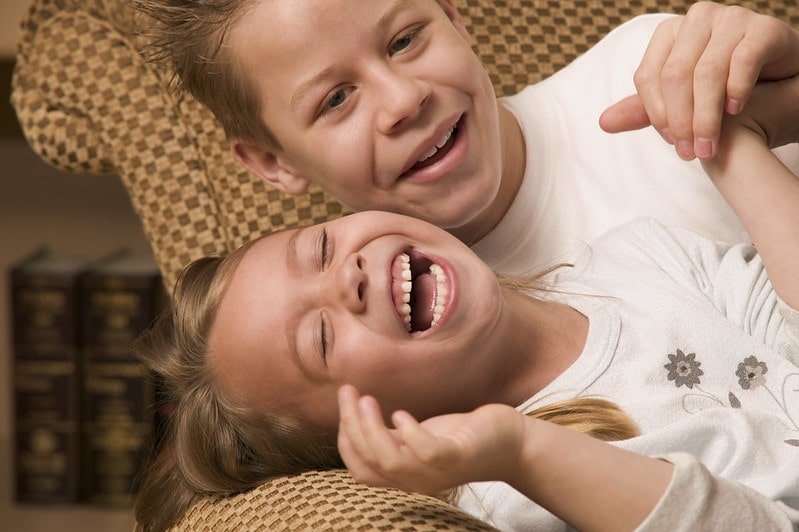 Boy and girl sat together laughing at jokes.