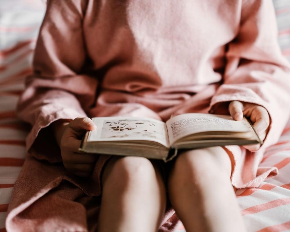 Girl reading books for Key Stage 1 readers