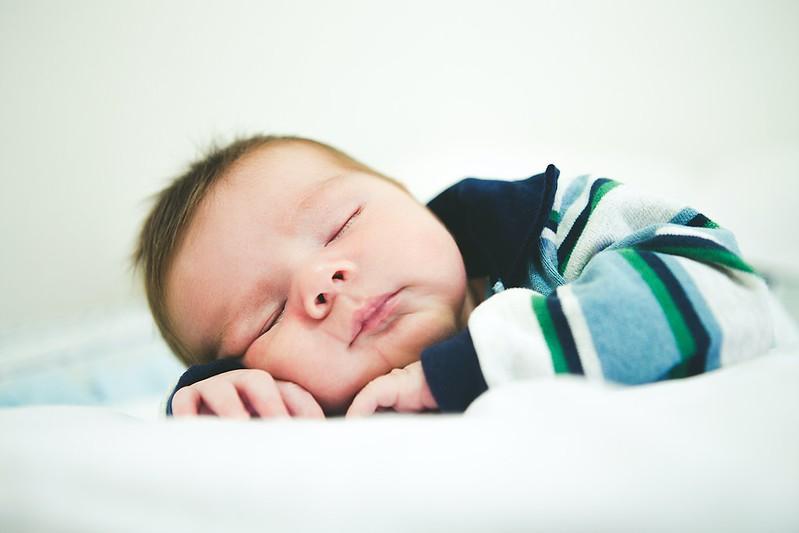 Baby boy wearing stripy top sleeping.