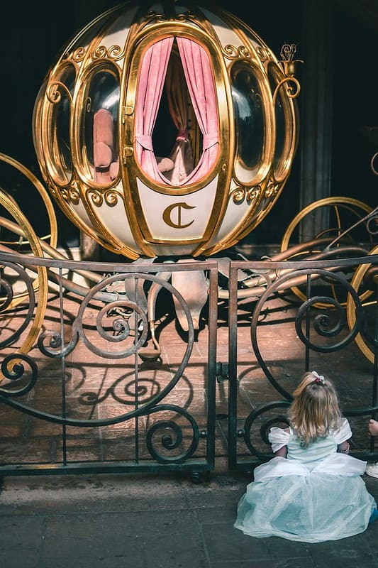 Little girl sitting at a Cinderella carriage.