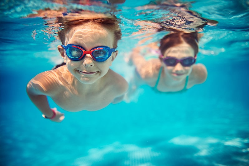 Little boy and girl swimming in the pool underwater wearing goggles.