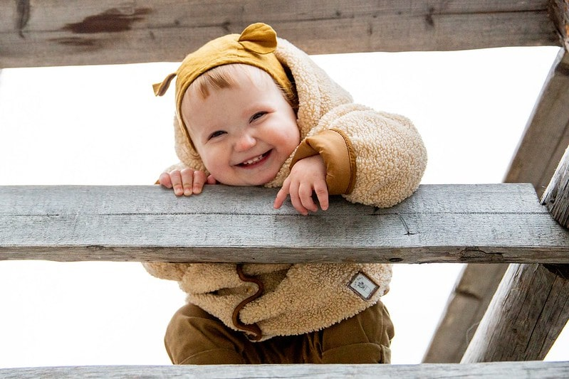 Happy baby wearing fluffy coat and bear hood on stairs.