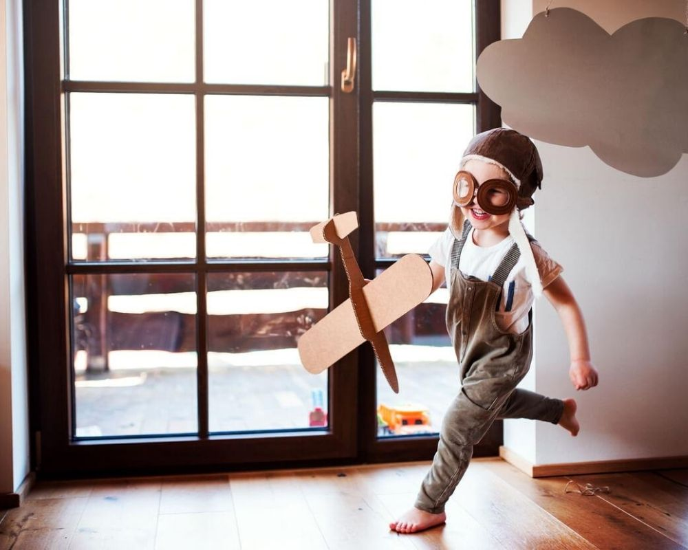 Boy playing with a cardboard plane