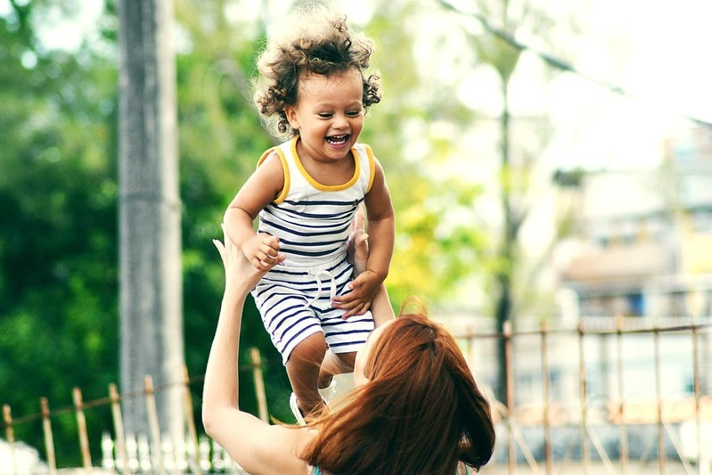 Mum lifts her smiling child up in the air.