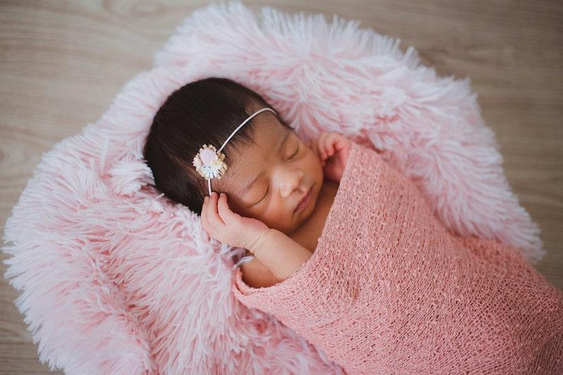 Newborn baby girl wearing a headband, wrapped in a pink blanket sleeping.