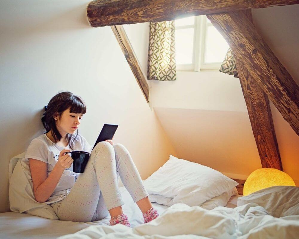 A teenager reads a book in bed.