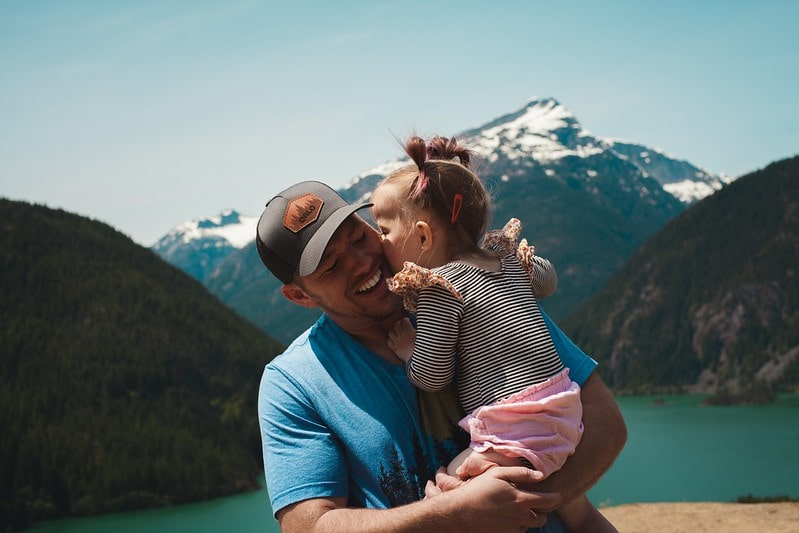 Baby girl in dad's arms giving him a kiss with beautiful mountains behind them.