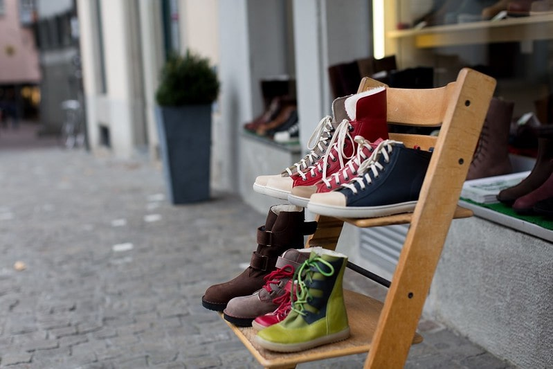 Pairs of shoes on a chair outside a shop window.