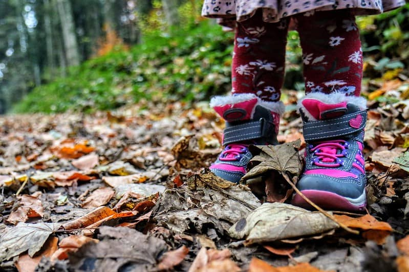 A little girl's boots while on a walk in the woods.
