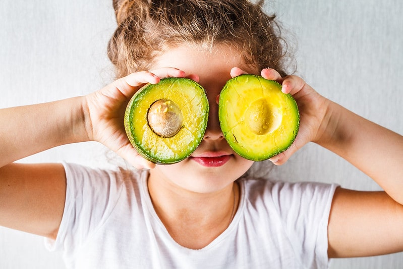Young girl messing around holding avocado halves in front of her eyes.