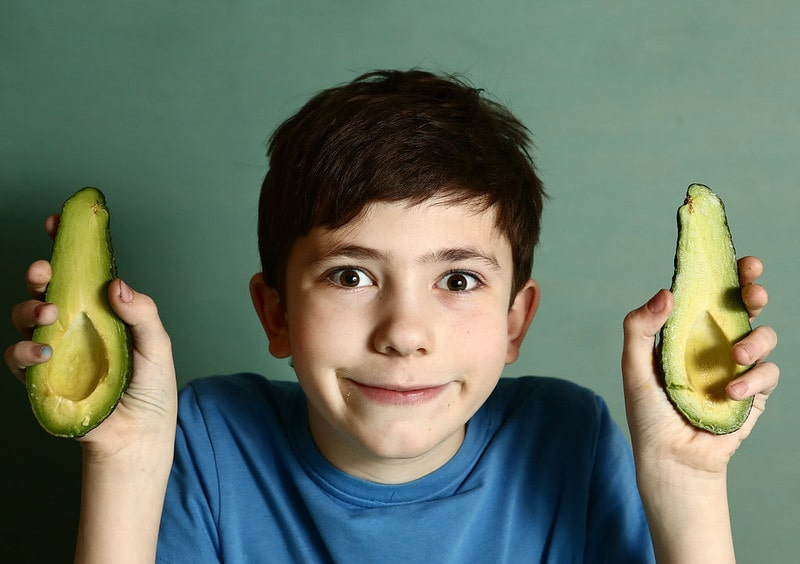 Young boy holding half an avocado in each hand making a silly face.
