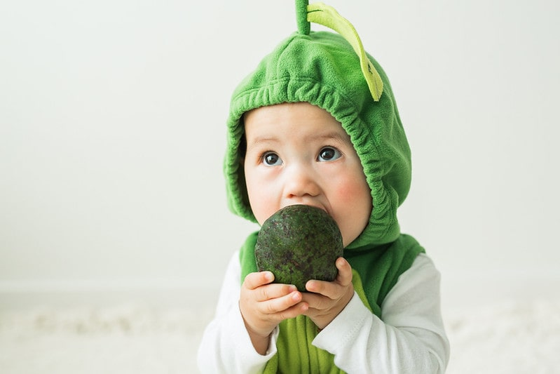 Baby wearing an avocado costume tries to eat a whole avocado.